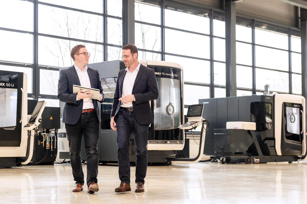 Zwei Geschäftsmänner im Anzug laufen durch eine energieeffiziente Produktionshalle mit dem OPTENDA Energie Monitor in ihren Händen.