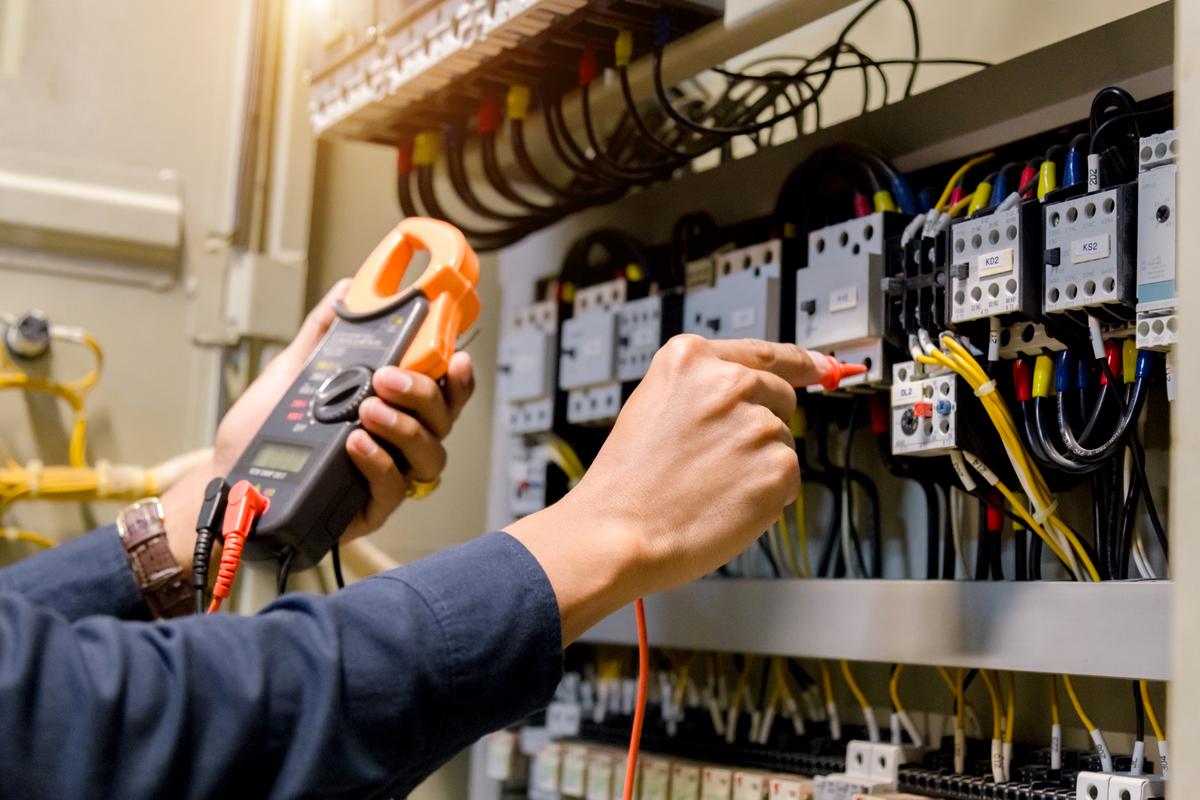 Mann überprüft Elektrotechnik zu Messung der Spannung und des Stroms