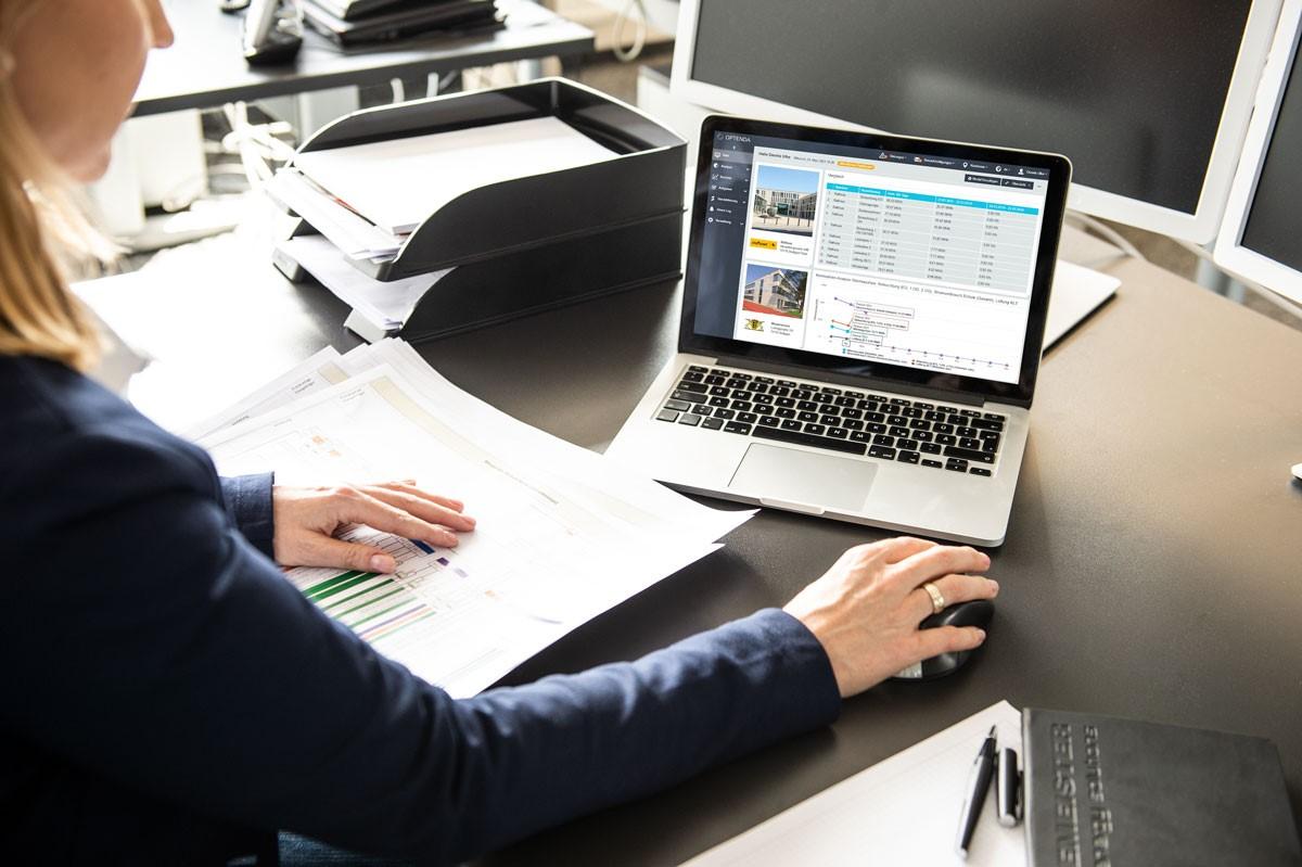 Frau sitzt am Schreibtisch und schaut auf einen Laptop, auf dessen Bildschirm der Energy Monitor von OPTENDA geöffnet ist